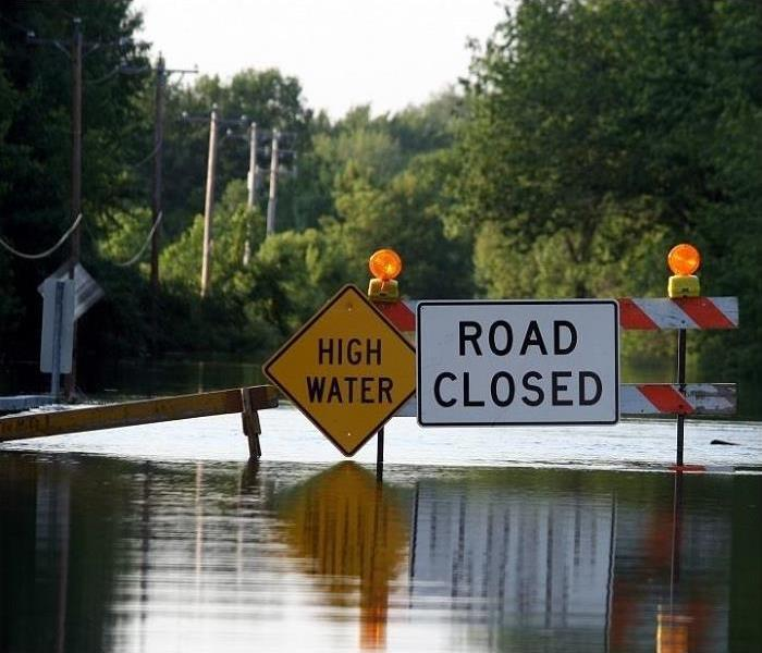 Road closed sign across flooded road