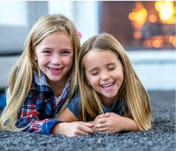 Two girls laying on carpet. Fireplace in background