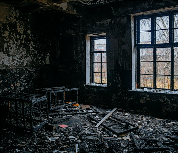 a room covered with soot and remains of burned items
