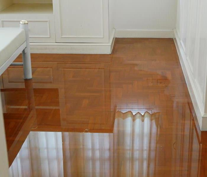 A white room with water on the wood flooring.